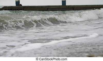 Foamy sea waves spreading over the beach in cloudy wather -...