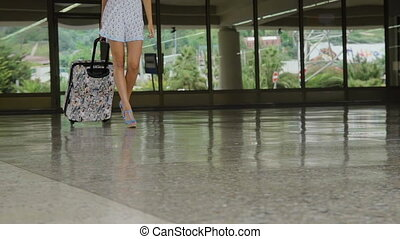 Legs of pretty woman with luggage and dressed in high hills shoes and dress