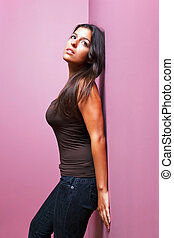 Woman leaning against a wall - An attractive brunette woman...
