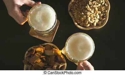 Two hands with mugs of beer. Nuts and crackers