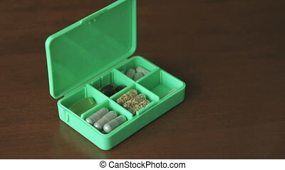 Woman's hand puts capsules tablets in container