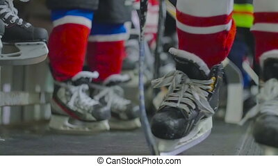 Young hockey players prepare for the game skates and sticks