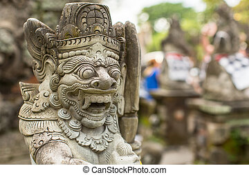 Traditional demon statue carved in stone on Bali island,...