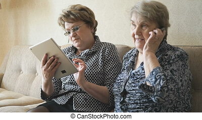 Old woman talking on smartphone at home