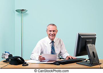 Mature businessman sat at his office desk - Mature...