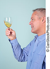 Man holding a glass of white wine checking it\'s clarity