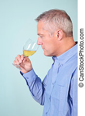 Man smelling a glass of white wine