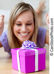 Happy woman looking at a gift lying on the floor