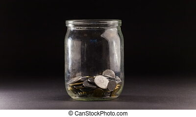 Time Lapse of Falling Coins in the Jar on Black background....