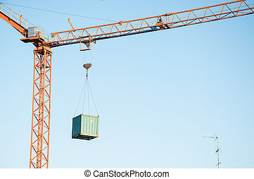 Crane at a construction site with a container...