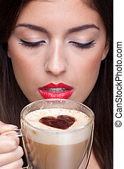Woman drinking cappuccino coffee with love heart shape
