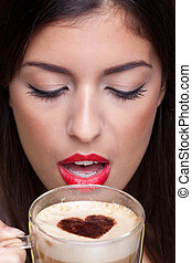 Woman drinking cappuccino coffee with love heart shape -...