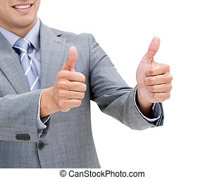 Close-up of a young businessman with thumbs up against a...