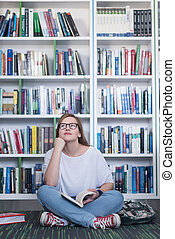 famale student reading book in library - smart looking...