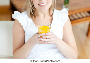 Smiling woman drinking an orange juice