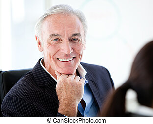 Charismatic senior businessman in a meeting with his team