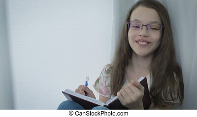 Emotional little girl with glasses writes in diary and...