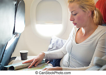 Woman reading magazine on airplane - Woman reading magazine...