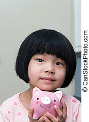 Asian child with piggy bank - Asian child hold a pink piggy...