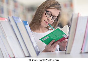 portrait of female student selecting book to read in library...
