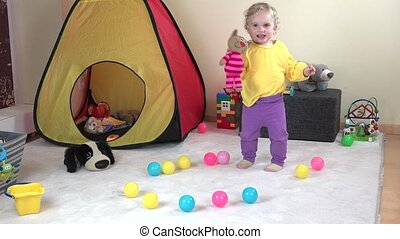 Active curly hair baby girl dancing with cute toy cat at home.