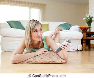 Beautiful blond woman watching TV lying on the floor at home...