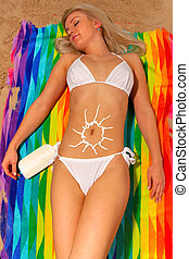 Woman sunbathing with suntan cream sun shape on her tummy