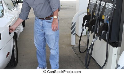Man Pumping Gas - Man opens tank on white car and pumps gas...
