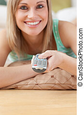 Jolly blond woman watching TV lying on the floor at home