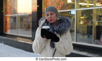 Young blonde drinking hot coffee on cold winter day - Young...