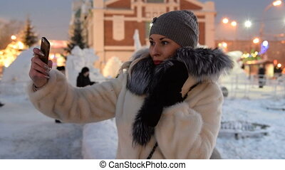 Girl taking selfie with mobile outdoor in winter evening -...