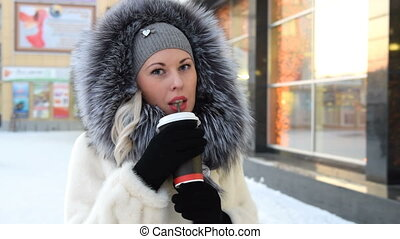 Girl drinking coffee on frosty winter day - Young blonde in...