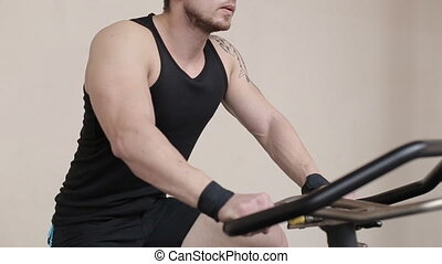 Fit man working out on exercise bike at the gym.