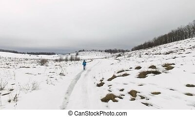 Tourist walks in snow field