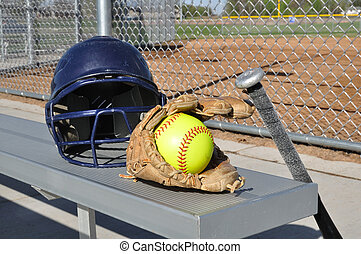 Yellow Softball, Helmet, Bat, and Glove on an Aluminum Bench