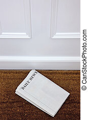 Blank newspaper lying on a doormat - Newspaper lying on a...