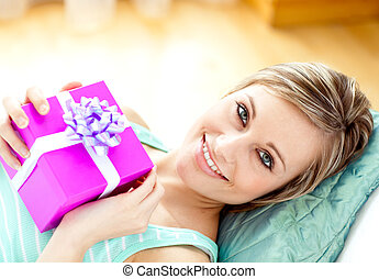 Smiling woman looking at a gift lying on the sofa at home