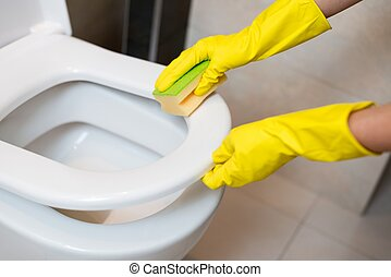 cleaning toilet seat - Hands with yellow rubber gloves...