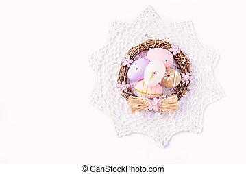 Easter eggs painted in pastel colors in the nest on white...