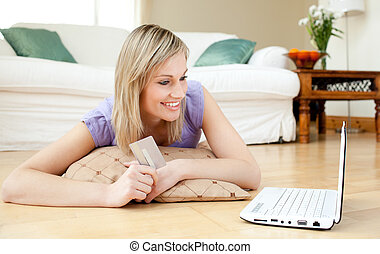 Jolly woman shopping on-line lying on the floor at home