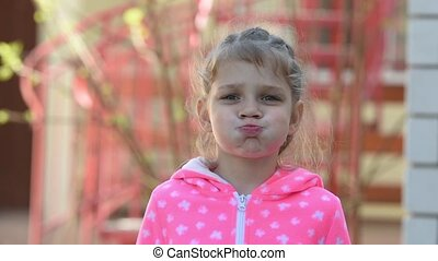 Girl five years old funny inflates cheeks