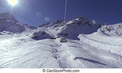 Chairlift POV going up a ski resort