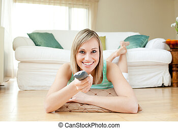 Young woman watching TV lying on the floor at home