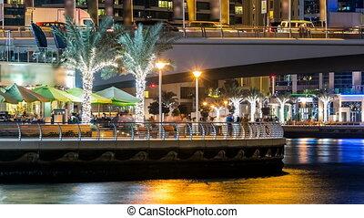 Promenade in Dubai Marina timelapse at night, UAE. -...