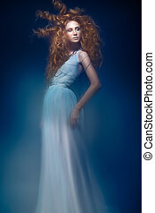 Beautiful fashionable red-haired girl in transparent dress,...