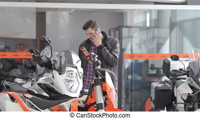 Consultant talks on the phone at motorbike salon - Brunette...