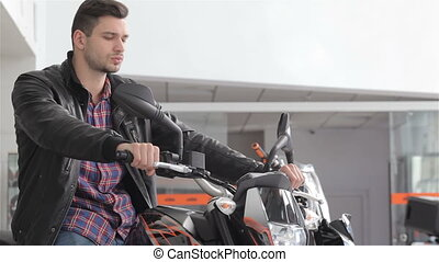 Man poses on motorbike - Close up of young dealer lookig...
