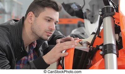 Young man looks at sport motorbike - Close up of man looking...