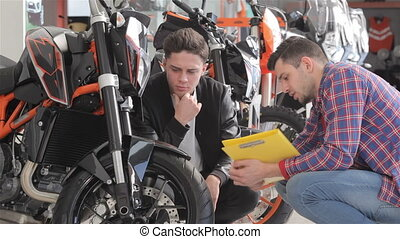 Customer talks with consultant about the motorbike - Two...