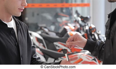 Close up of buyer getting motorbike key - Close up of...
